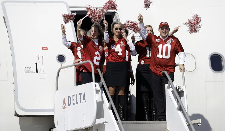 The flight crew for the University of Alabama waves pompoms after the team arrived at Tampa International Airport Friday, Jan. 6, 2017, in Tampa, Fla. Alabama takes on Clemson Monday in the College Football Playoff championship game. (AP Photo/Chris O'Meara)