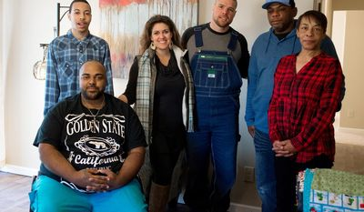 ADVANCE FOR SUNDAY, JAN. 8, 2017- In this Dec. 30, 2016 photo, the Parker family, father Odie, second from right, mother Stacy right, children Shea, background left, and Trevon, left, pose with  Julie Martin Richard, and Richard's husband building contractor Jonathon, in their repaired home which was damaged by Hurricane Matthew, in Hope Mills, N.C. (Melissa McKinney /The Fayetteville Observer via AP)