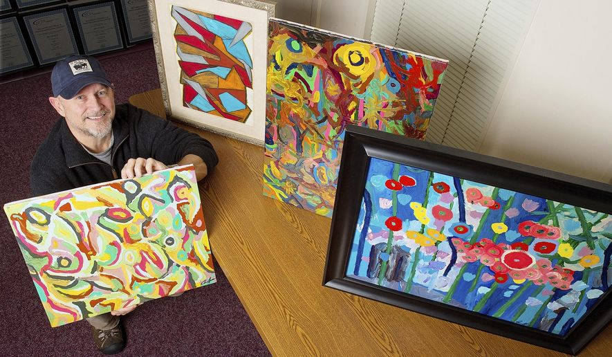 Darren Moore poses with some of his abstract paintings on Tuesday, Jan. 3, 2017, in Lexington, N.C. that he began creating as a hobby about eight years ago. Shown are samples of oil pastels, upper left, and acrylics. (Donnie Roberts/The Dispatch via AP)