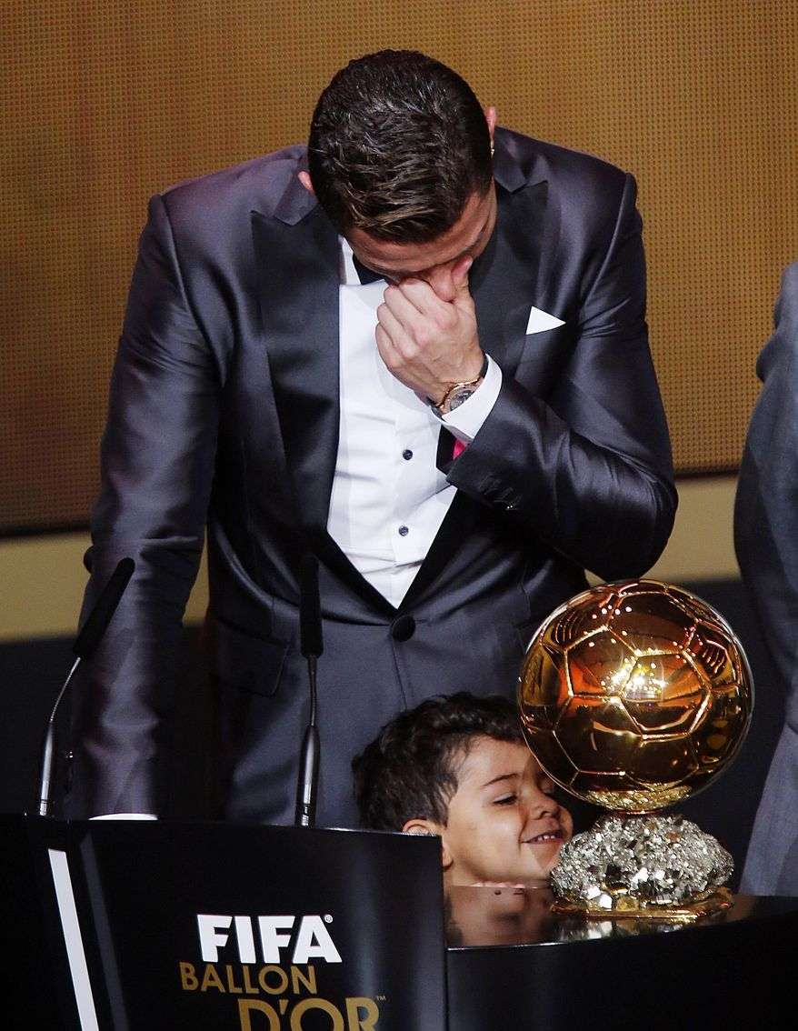 FILE - In this Monday, Jan. 13, 2014 file photo, Real Madrid's Christiano Ronaldo of Portugal cries next to his son Ronaldo Junior after receiving the trophy for the world player at the FIFA Ballon d'Or 2013 Gala in Zurich, Switzerland. Cristiano Ronaldo is the strong favorite to be named the world's best player for the fourth time by FIFA on Monday Jan. 9, 2017. (AP Photo/Michael Probst, File)