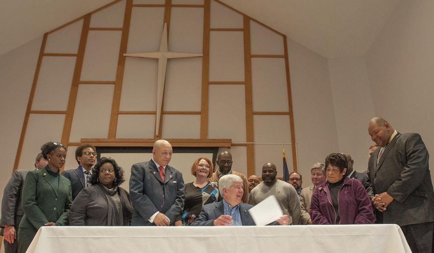 Michigan Gov. Rick Snyder signs the first piece of legislation emanating from the Flint water crisis at Grace Emmanuel Church in Flint, Mich., Friday, Jan. 6, 2017. Flint Democratic Rep. Neeley, left with red tie, who was a city council member when the city switched to the Flint River in April 2014, was the sponsor of the bill. Snyder signed the legislation forcing utilities to more quickly warn customers if there is too much lead in their water. (John M. Galloway/Detroit News via AP)