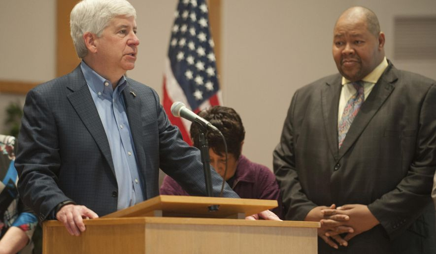 Michigan Gov. Rick Snyder speaks where he signed the first piece of legislation emanating from the Flint water crisis at Grace Emmanuel Church in Flint, Mich., Friday, Jan. 6, 2017. At right is Flint City Council president Kerry Nelson.  Snyder signed the legislation forcing utilities to more quickly warn customers if there is too much lead in their water. (John M. Galloway/Detroit News via AP)