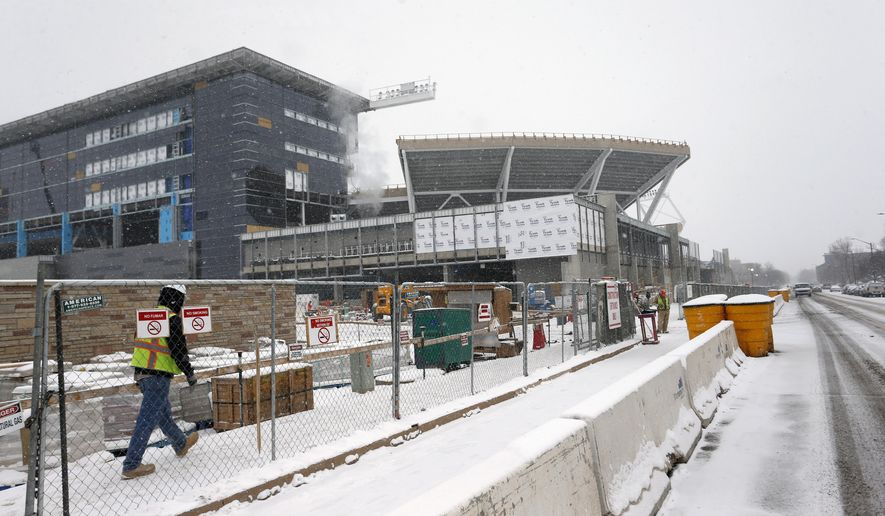 In this Jan. 4, 2017, photo, construction work continues in the snow at the site of Colorado State University's new football stadium in Fort Collins, Colo. With a new, $220 million stadium almost complete, Colorado State is one of a handful of schools that have recently committed major resources to football.  (AP Photo/Brennan Linsley)