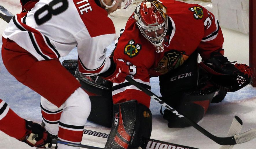 Chicago Blackhawks goalie Scott Darling, right, blocks a shot by Carolina Hurricanes right wing Ty Rattie during the third period of an NHL hockey game Friday, Jan. 6, 2017, in Chicago. (AP Photo/Nam Y. Huh)