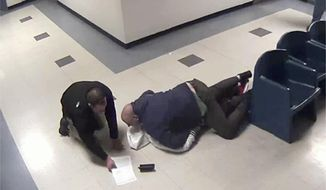 This Jan. 28, 2014 still image from jail surveillance video, provided by attorney Matthew Hoppock, shows two immigration agents in an altercation with Justine Mochama, an international student from Kenya who overstayed his visa, for refusing to be fingerprinted before deportation at the Butler County Detention Facility in El Dorado, Kan. Mochama filed a lawsuit alleging he was violently attacked by the agents and won a rare legal victory Tuesday, Jan. 3, 2017, when a federal judge ruled that his lawsuit could go to trial over the incident captured on jailhouse surveillance video. (Butler County Detention Facility surveillance video provided by attorney Matthew Hoppock via AP)