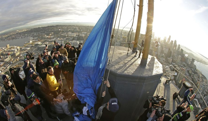 Former Seattle Seahawks quarterback Dave Krieg, center, raises a Seahawks 12 flag on the roof of the Space Needle, Friday, Jan. 6, 2017, in Seattle. The Seahawks will host the Detroit Lions Saturday in an NFL football NFC wild card playoff football game. (AP Photo/Ted S. Warren)