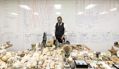 In a Tuesday, Dec. 6, 2016 photo, James Washington, of the Houston Museum of Natural Science talks about his shell collection in front of a chart he made, in Houston.  Washington's tours are a blend of science, jokes and pop culture references. (Elizabeth Conley//Houston Chronicle via AP)
