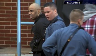 In this image made from a video provided by WCVB-TV, Massachusetts State Police lead James Morales, left, into the barracks in Medford, Mass., Thursday, Jan. 5, 2017. Morales, who escaped from a Rhode Island detention center on New Year's Eve, tried to rob a bank in Somerville, Mass., just before he was captured. When he escaped, he was being held on charges that he stole guns from a U.S. Army Reserve Center in Worcester, Mass. (Stanley Forman/WCVB-TV via AP) MANDATORY CREDIT; BOSTON OUT; PROVIDENCE OUT