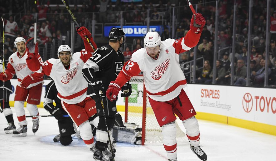 Detroit Red Wings left wing Thomas Vanek, right, of Austria, celebrates his goal along with defenseman Jonathan Ericsson, left, of Sweden, and center Andreas Athanasiou, right, as Los Angeles Kings defenseman Alec Martinez skates by during the first period of an NHL hockey game, Thursday, Jan. 5, 2017, in Los Angeles. (AP Photo/Mark J. Terrill)
