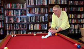 In this Dec. 28, 2016, photo, Nils Sharpe uses his ramp invention, replacing a cue stick, during a game of pool at Carson Plaza in Carson City, Nev. The Nevada Appeal reported that Sharpe invented a small ramp for pool tables that helps people play the game even if they can't stand for long or bend. (Molly Moser/Nevada Appeal via AP)