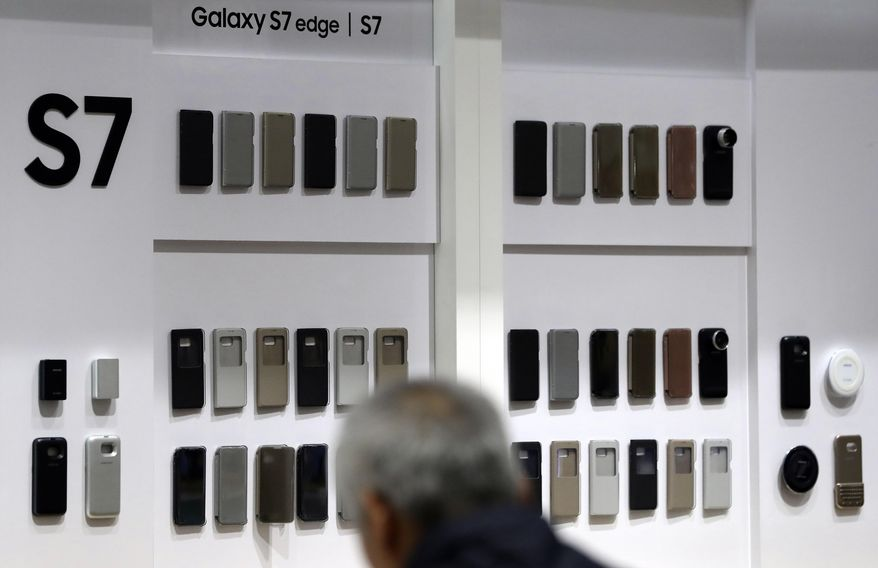 A visitor looks at the smartphone cases of Samsung Electronics Galaxy S7 and S7 edge smartphones at its shop in Seoul, South Korea, Friday, Jan. 6, 2017. Samsung Electronics Co. said Friday that its profits in the last quarter of 2016 surged 50 percent to the highest level in more than three years, despite the Galaxy Note 7 fiasco. (AP Photo/Lee Jin-man)