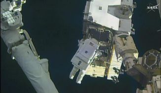 In this still image taken from video provided by NASA, astronaut Peggy Whitson takes a spacewalk outside the International Space Station on Friday, Jan. 6, 2016.  Whitson and Commander Shane Kimbrough went spacewalking  to hook up fancy new batteries on the International Space Station's sprawling power grid.(NASA via AP)