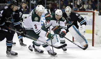 Minnesota Wild's Charlie Coyle (3) reaches for the puck next to San Jose Sharks' Brenden Dillon (4) during the second period of an NHL hockey game Thursday, Jan. 5, 2017, in San Jose, Calif. (AP Photo/Marcio Jose Sanchez)