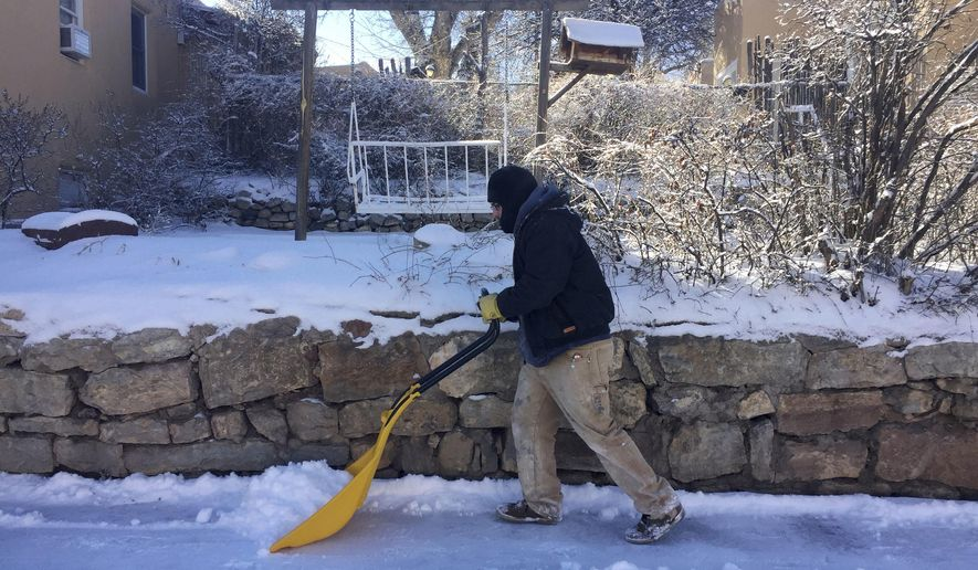 Laborer Guillermo Perez, of Santa Fe, N.M, clears sidewalks and driveways as residents dig out from a winter storm that closed schools and blanketed nearby ski resorts with snow on Friday, Jan. 6, 2017. Authorities reported difficult driving conditions on the state's two main interstate highways. (AP Photo/Morgan Lee)
