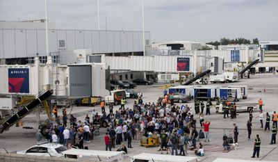 People stand on the tarmac at the Fort Lauderdale-Hollywood International Airport after a shooter opened fire inside a terminal of the airport, killing several people and wounding others before being taken into custody, Friday, Jan. 6, 2017, in Fort Lauderdale, Fla. (AP Photo/Wilfredo Lee)