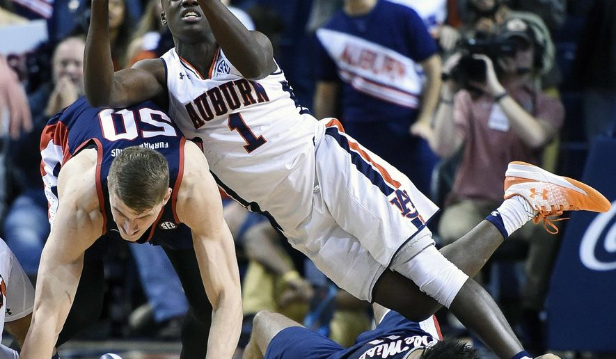 Auburn guard Jared Harper (1) trips over Mississippi forward Justas Furmanavicius (50) and forward Sebastian Saiz (11) during an NCAA college basketball game, Saturday, Jan. 7, 2017 in Auburn, Ala. (Julie Bennett/AL.com via AP)