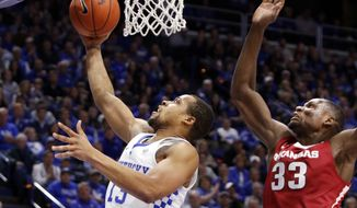Kentucky's Isaiah Briscoe, left, shoots while defended by Arkansas' Moses Kingsley (33) during the first half of an NCAA college basketball game, Saturday, Jan. 7, 2017, in Lexington, Ky. (AP Photo/James Crisp)