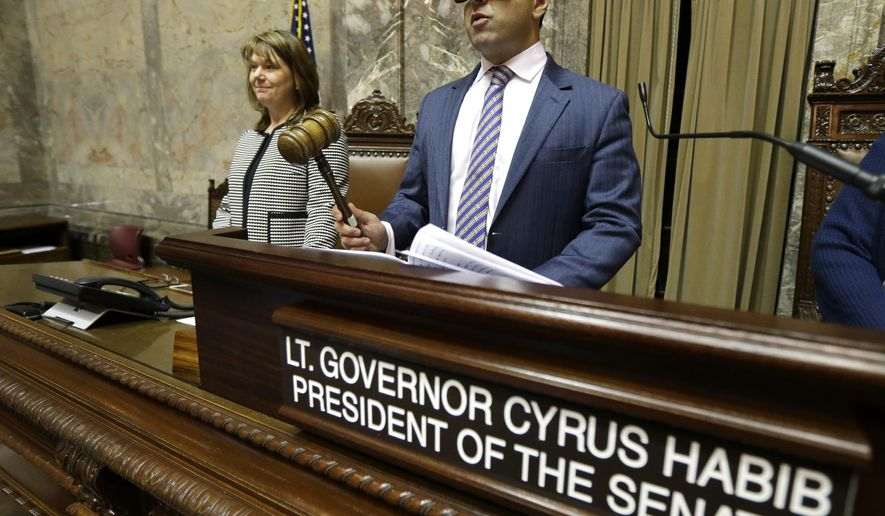 Washington Lt. Gov.-elect Cyrus Habib, right, holds the gavel as he stands at the Senate chamber dais next to Senate Counsel Jeannie Gorrell, left, Thursday, Jan. 5, 2017, during a practice session to test technical equipment in Olympia, Wash. Habib, who will preside over the Senate, will be Washington's first blind lieutenant governor, and the Senate has undergone a makeover that incorporates Braille into that chamber's floor sessions that will allow Habib to know by the touch of his finger which lawmaker is seeking to be recognized to speak. Habib is replacing Lt. Gov. Brad Owen, who is retiring. (AP Photo/Ted S. Warren)