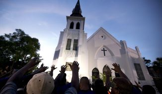 FILE -In this Friday, June 19, 2015 file photo, the men of Omega Psi Phi Fraternity Inc. lead a crowd of people in prayer outside the Emanuel AME Church, after a memorial for the nine people killed by Dylann Roof in Charleston, S.C. A federal jury will consider whether Roof should be sentenced to death or life in prison for the racially motivated attack.(AP Photo/Stephen B. Morton, File)