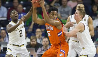 Clemson's Jaron Blossomgame (5) gets pressure from Notre Dame's T.J. Gibbs (2), Rex Pflueger, right, and Austin Torres during the first half of an NCAA college basketball game Saturday, Jan. 7, 2017, in South Bend, Ind. (AP Photo/Robert Franklin)