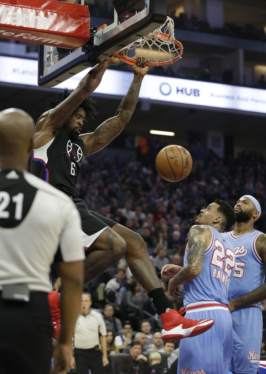 LA Clippers center DeAndre Jordan, left, hangs on the rim after stuffing over Sacramento Kings' Matt Barnes, center, and DeMarcus Cousins during the first half of an NBA basketball game Friday, Jan. 6, 2017, in Sacramento, Calif. (AP Photo/Rich Pedroncelli)