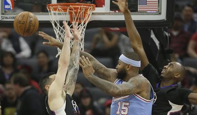 Sacramento Kings forward DeMarcus Cousins, center, passes out of the double team of Los Angeles Clippers' J.J. Redick, left, and Luc Mbah a Moute during the first half of an NBA basketball game Friday, Jan. 6, 2017, in Sacramento, Calif.(AP Photo/Rich Pedroncelli)