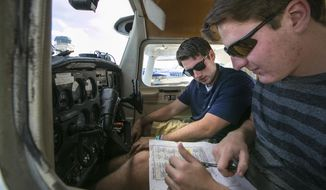 ADVANCE FOR WEEKEND EDITIONS, JAN. 7 -8 - In this Dec. 15, 2016 photo, instructor David Kissel, right, and Trinity Catholic High School senior Clayton Wilson go over the checklist as they prepare for an afternoon instruction flight at Ocala Aviation at the Ocala International Airport in Ocala, Fla. Trinity Catholic students can get their private pilots license for a much cheaper cost through taking classes ground study classes through the hight school and flight training through Ocala Aviation. Wilson is expected to get his license before the end of the year. (Alan Youngblood/Star-Banner via AP)