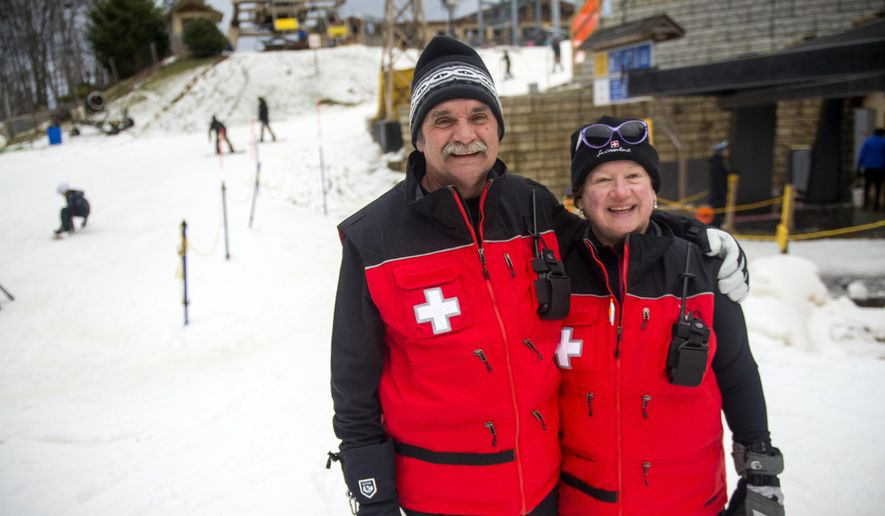 In this Saturday, Dec. 31, 2016 photo, Ski Patrol members Peter and Joy Juker pause on the slopes at the Ober Gatlinburg resort in Gatlinburg, Tenn. The Gatlinburg wildfire took the house they owned, along with the homes of two other ski patrol members. (Brianna Paciorka/Knoxville News Sentinel via AP)