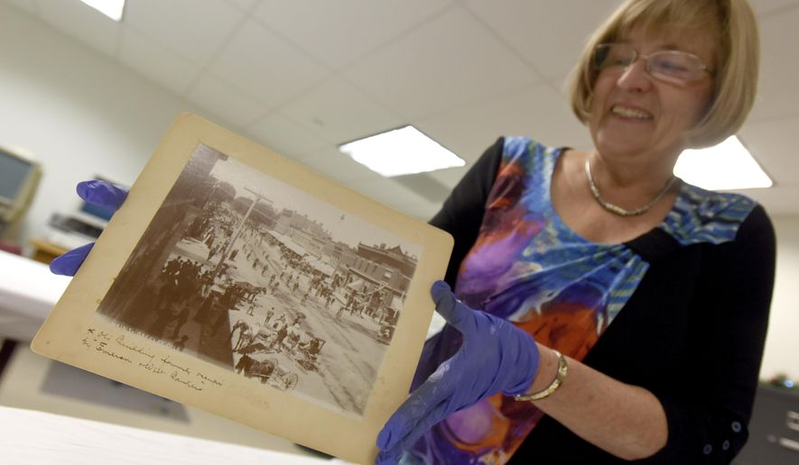 ADVANCE FOR USE SATURDAY, JAN. 7 - In this Dec. 12, 2016 photo, Peggy Ford Waldo smiles as she pulls one of the photos used in a book she wrote with the help of the Greeley History Museum at the musuem in Greeley, Colo. Waldo has worked for the Greeley History Museum since 1979 and is considered the city's most knowledgeable historian. (Joshua Polson /The Greeley Tribune via AP)