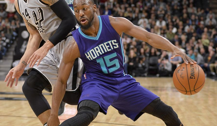 Charlotte Hornets guard Kemba Walker (15) drives around San Antonio Spurs guard Danny Green during the first half of an NBA basketball game, Saturday, Jan. 7, 2017, in San Antonio. (AP Photo/Darren Abate)