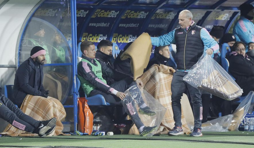 Palermo players receive blankets to shelter from the cold prior to the start of a Serie A soocer match between Empoli and Palermo, at the Carlo Castellani stadium in Empoli, Italy, Saturday, Jan. 7, 2017. Strong winds, snowfalls and unusually low temperatures have been hitting Italy for the last two days. (Fabio Muzzi/ANSA via AP)