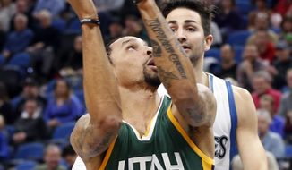 Utah Jazz's George Hill, left, in view of Minnesota Timberwolves' Ricky Rubio, of Spain, eyes a shot  during the first quarter of an NBA basketball game Saturday, Jan. 7, 2017, in Minneapolis. (AP Photo/Jim Mone)