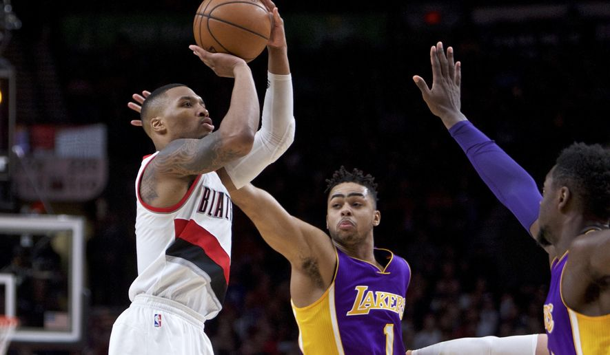 Portland Trail Blazers guard Damian Lillard, left, shoots over Los Angeles Lakers guard D'Angelo Russell, center, and forward Julius Randle, right, during the second half of an NBA basketball game in Portland, Ore., Thursday, Jan. 5, 2017. The Trail Blazers won 118-109. (AP Photo/Craig Mitchelldyer)