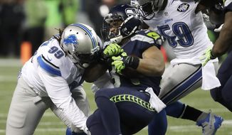 Seattle Seahawks running back Thomas Rawls, center, is tackled by Detroit Lions defensive tackle Khyri Thornton (99) and Lions middle linebacker Tahir Whitehead (59) in the first half of an NFL football NFC wild card playoff game, Saturday, Jan. 7, 2017, in Seattle. (AP Photo/Elaine Thompson)