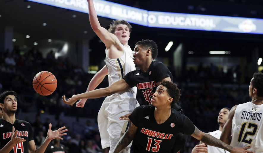 Louisville's Donovan Mitchell, center, passes the ball to teammate Anas Mahmoud, left, as Ray Spalding (13) helps on the play against the defense of Georgia Tech's Ben Lammers, rear, in the first half of an NCAA college basketball game in Atlanta, Saturday, Jan. 7, 2017. (AP Photo/David Goldman)