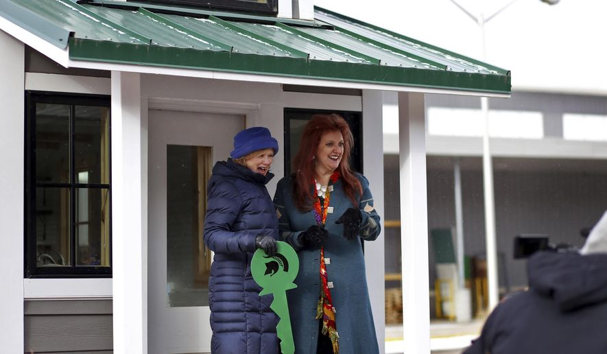 Provost June Youatt presents the keys to Sparty's Cabin to its new owner, MSU alumna Debra Levantrosser, at Surplus and Recycling Center on the campus of Michigan State University on Friday, Jan.6, 2017.  (Samantha Madar/Jackson Citizen Patriot via AP)