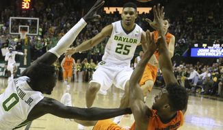 Oklahoma State forward Leyton Hammonds, right, passes the ball over Baylor forward Jo Lual-Acuil Jr., left, in the first half of an NCAA college basketball game, Saturday, Jan. 7, 2017, in Waco, Texas. (AP Photo/Rod Aydelotte)