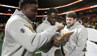 Clemson's John Simpson, Milan Richard and Gage Cervenka look at a tablet during media day for the NCAA college football playoff championship game against Alabama Saturday, Jan. 7, 2017, in Tampa, Fla. (AP Photo/Chris O'Meara)