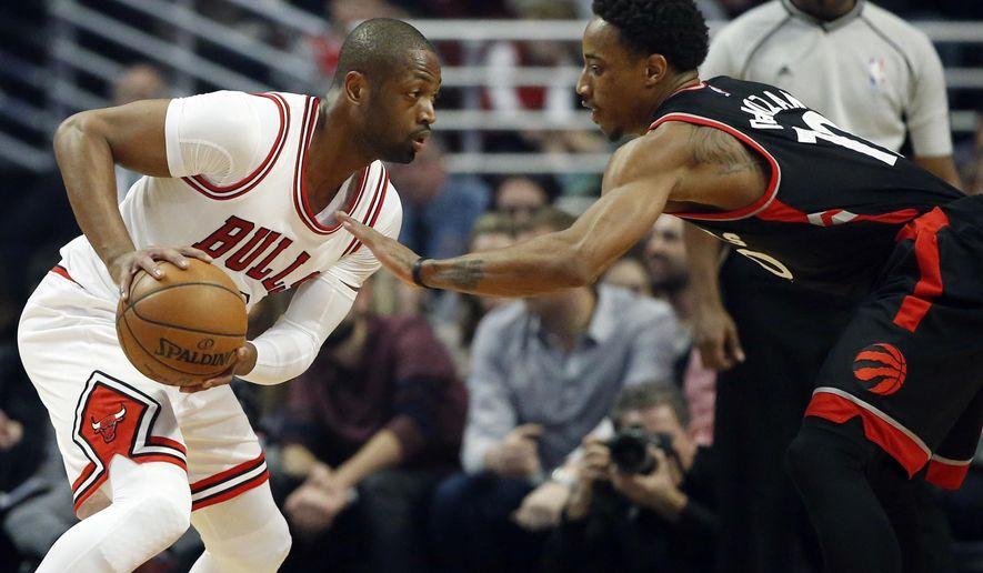 Chicago Bulls guard Dwyane Wade, left, drives against Toronto Raptors guard DeMar DeRozan during the first half of an NBA basketball game Saturday, Jan. 7, 2017, in Chicago. (AP Photo/Nam Y. Huh)