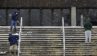 Workers shovel snow and sleet from the stairs outside the Dean E. Smith Center in preparation for tonight's NCAA basketball game between North Carolina and North Carolina State in Chapel Hill, N.C., Saturday, Jan. 7, 2017. (AP Photo/Gerry Broome)