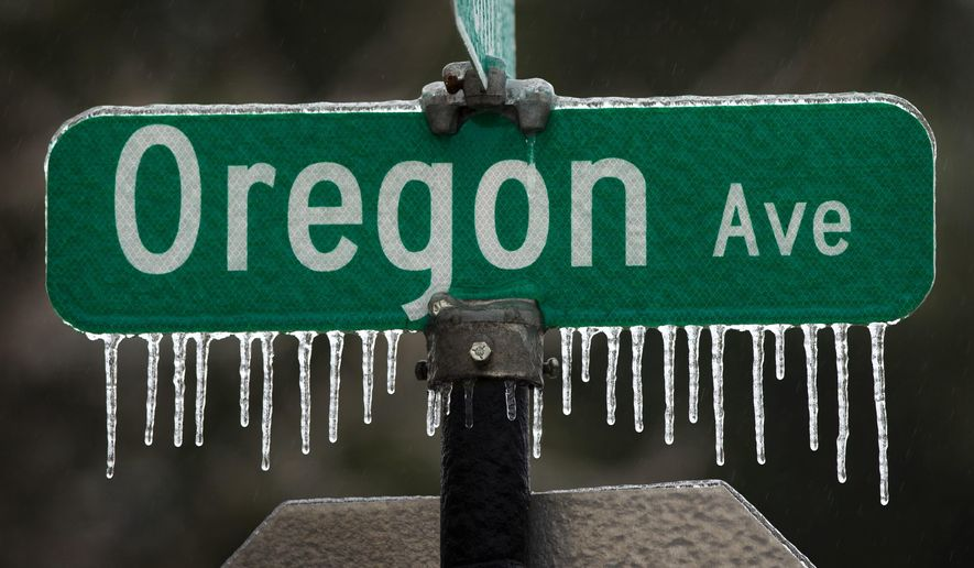 Icicles cling to a street sign in downtown Creswell, Ore. after a storm moved through the Willamette Valley Saturday Jan. 7, 2017. (Chris Pietsch/The Register-Guard via AP)