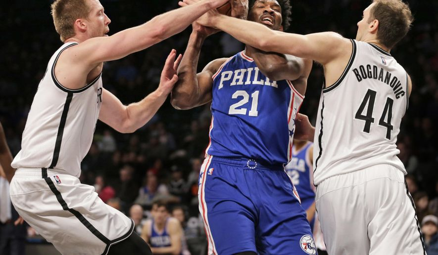 Philadelphia 76ers' Joel Embiid, center, is stopped by Brooklyn Nets' Justin Hamilton, left, and Bojan Bogdanovic during the first half of the NBA basketball game at the Barclays Center, Sunday, Jan. 8, 2017, in New York. (AP Photo/Seth Wenig)