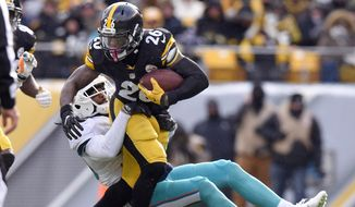 Pittsburgh Steelers running back Le'Veon Bell (26) runs through a tackle by Miami Dolphins free safety Bacarri Rambo during the first half of an AFC wild-card NFL football game in Pittsburgh, Sunday, Jan. 8, 2017. (AP Photo/Don Wright)