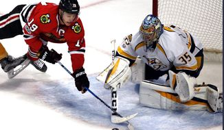Chicago Blackhawks center Jonathan Toews, left, and Nashville Predators goalie Pekka Rinne battle for the puck during the second period of an NHL hockey game Sunday, Jan. 8, 2017, in Chicago. (AP Photo/Nam Y. Huh)
