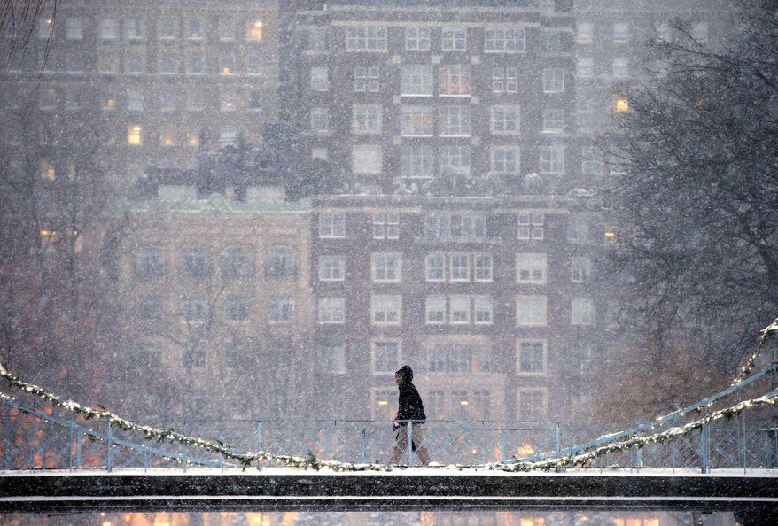 A person crosses the pedestrian bridge in the Public Garden during a winter storm in Boston, Saturday, Jan. 7, 2017. (AP Photo/Michael Dwyer)