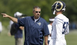 FILE - In this Aug. 1, 2015, file photo, St. Louis Rams defensive coordinator Gregg Williams, left, talks with middle linebacker James Laurinaitis during NFL football training camp in St. Louis. The Cleveland Browns have hired Williams to fix a defense that was among the NFL's worst in 2016. (AP Photo/Jeff Roberson, File)
