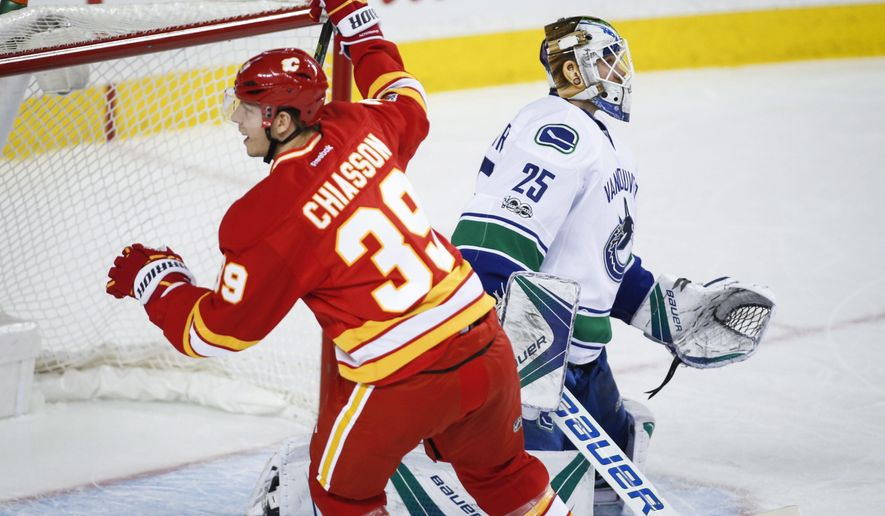Vancouver Canucks goalie Jacob Markstrom, right, of Sweden, looks away as Calgary Flames' Alex Chiasson celebrates his goal during third-period NHL hockey game action in Calgary, Alberta, Saturday, Jan. 7, 2017. (Jeff McIntosh/The Canadian Press via AP)