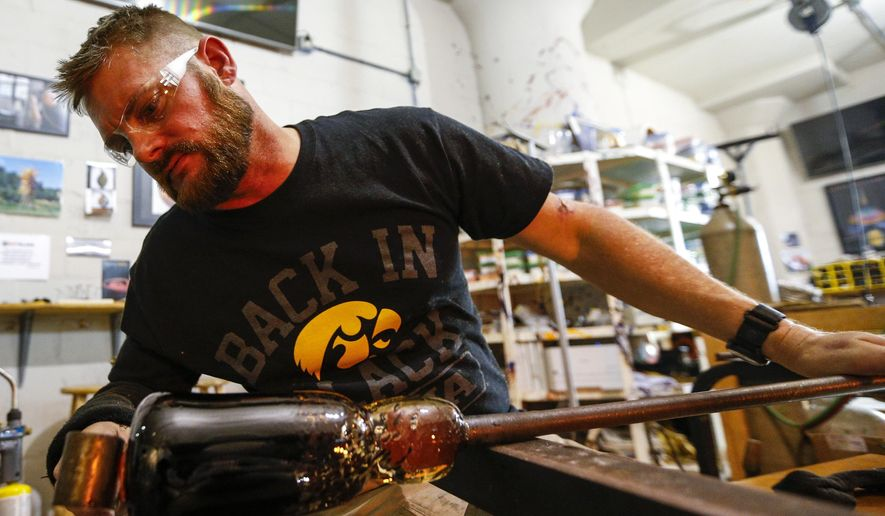 ADVANCE FOR THE WEEKEND OF JAN. 7-8 AND THEREAFTER - In a Dec. 21, 2016 photo, Mark Van Osdel of Le Claire uses a paddle to shape the base of his vase and prep it to transfer from the pipe to a ponty at Hot Glass studio in Davenport. Van Osdel is a veteran who is currently learning the art form from Joel Ryser who runs Hot Glass, a nonprofit organization and business in Davenport that offers free glass-blowing classes to veterans and at-risk children. (Andy Abeyta/Quad City Times via AP)