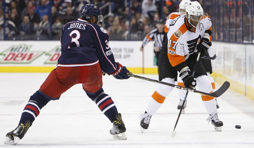 Philadelphia Flyers' Wayne Simmonds, right, carries the puck across the blur line as Columbus Blue Jackets' Seth Jones defends during the third period of an NHL hockey game Sunday, Jan. 8, 2017, in Columbus, Ohio. The Blue Jackets beat the Flyers 2-1 in overtime. (AP Photo/Jay LaPrete)