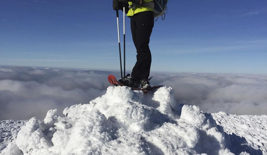 """In this Dec. 6, 2016 photo, Sue Johnston poses on top of Mount Eisenhower in the White Mountains of New Hampshire. Johnston is believed to be the first person to complete an ambitious hiking challenge in the White Mountains in a single year. The Concord Monitor reported Johnston hiked every one of New Hampshire's 4,000-foot mountains in every single month of the year in 2016. The challenge is known as """"the Grid"""" and takes most hikers years to complete. (Chris Scott via AP)"""